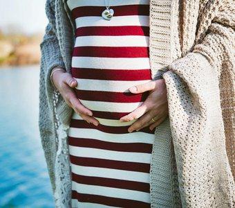 e5bd0aeb1ae20a Eine Schwangere in gestreiftem Kleid legt ihre Hände auf ihren Bauch